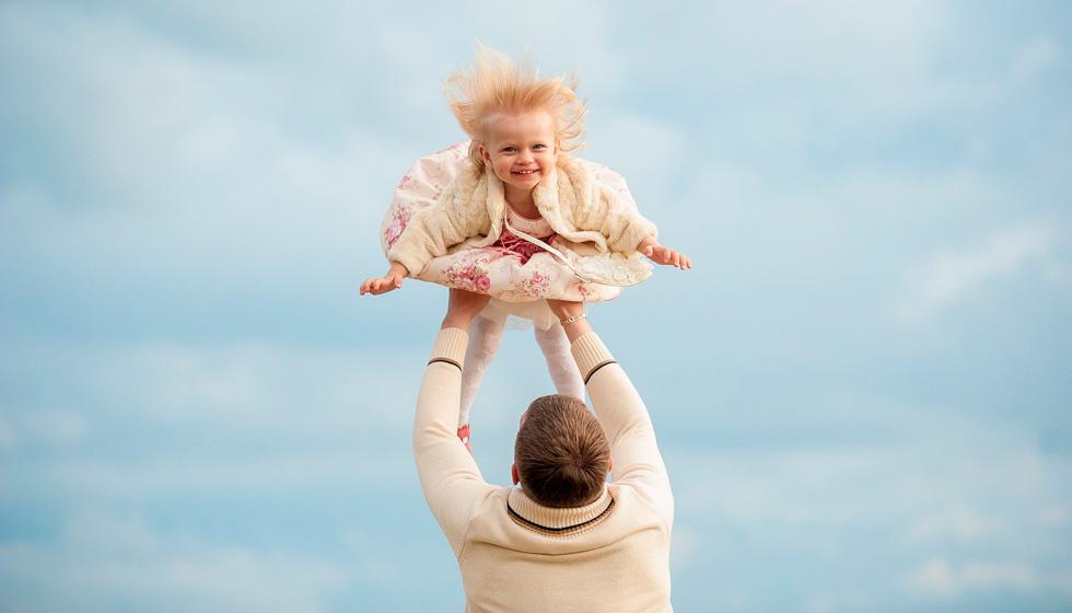 папа подкидывает девочку на руках