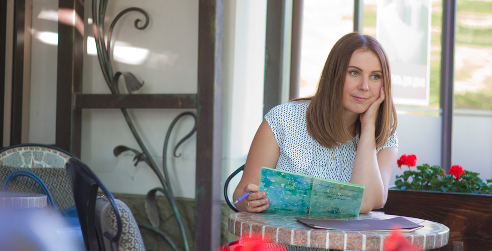Яна Катаева за столиком с блокнотом