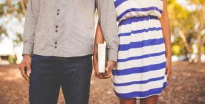 Мужчина и женщина держатся за руки, в руках книга
