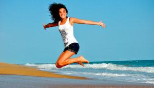 Девушка высоко подпрыгнула на пляже