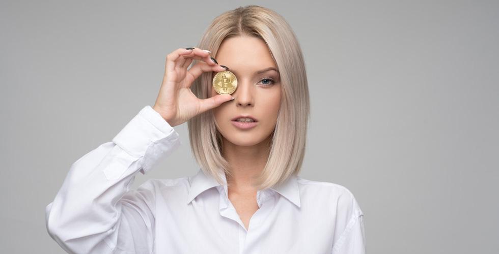 Девушка держит монету у лица