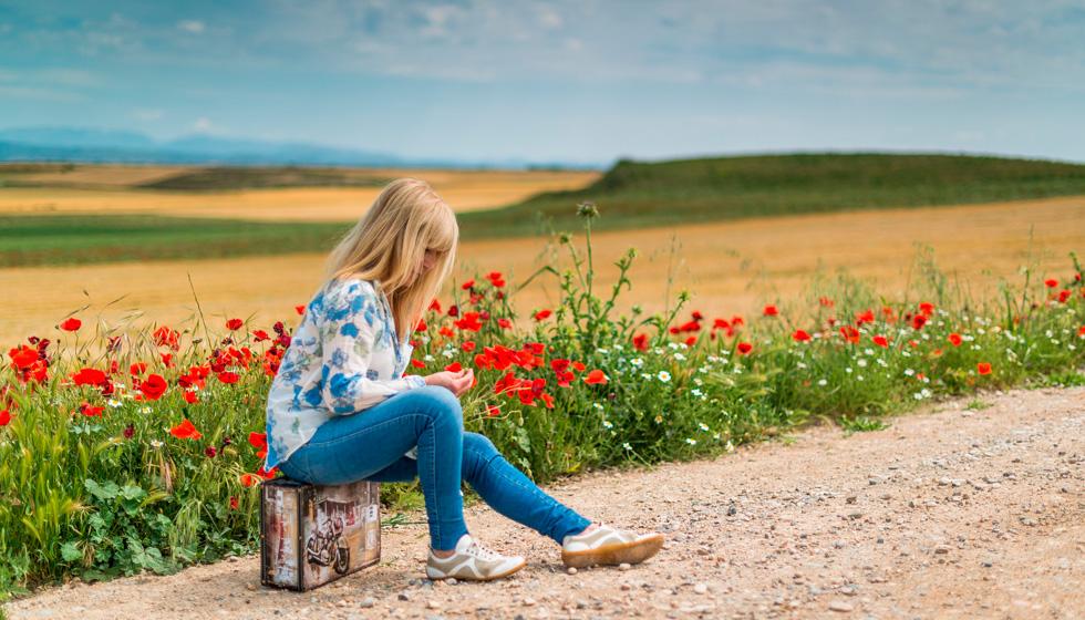 женщина на дороге сидит на чемодане