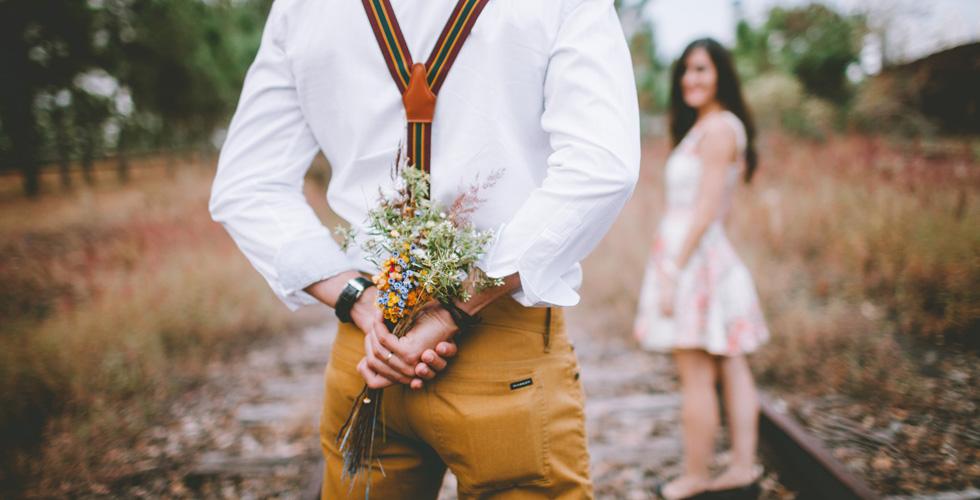 Мужчина держит за спиной цветы