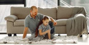 папа с дочкой играют на ковре