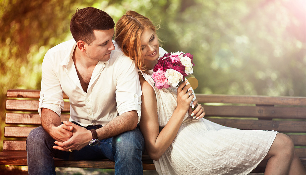 мужчина и женщина с букетом на скамье