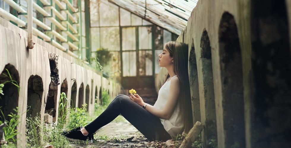 девушка сидит в развалинах