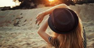 Девушка в шляпе закрывается от солнца
