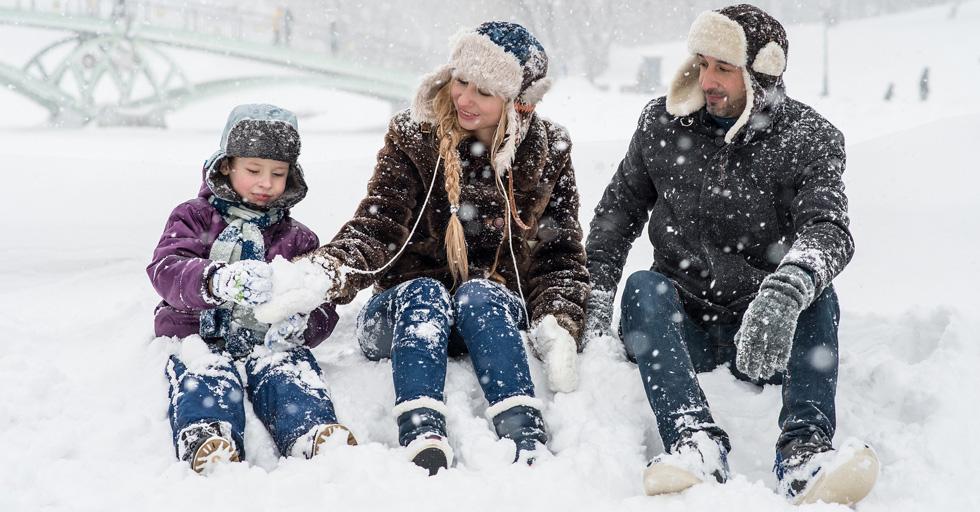Семья гуляет зимой, сидят на снегу