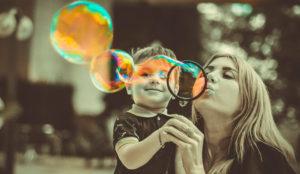 мама с ребенком играют в мыльные пузыри
