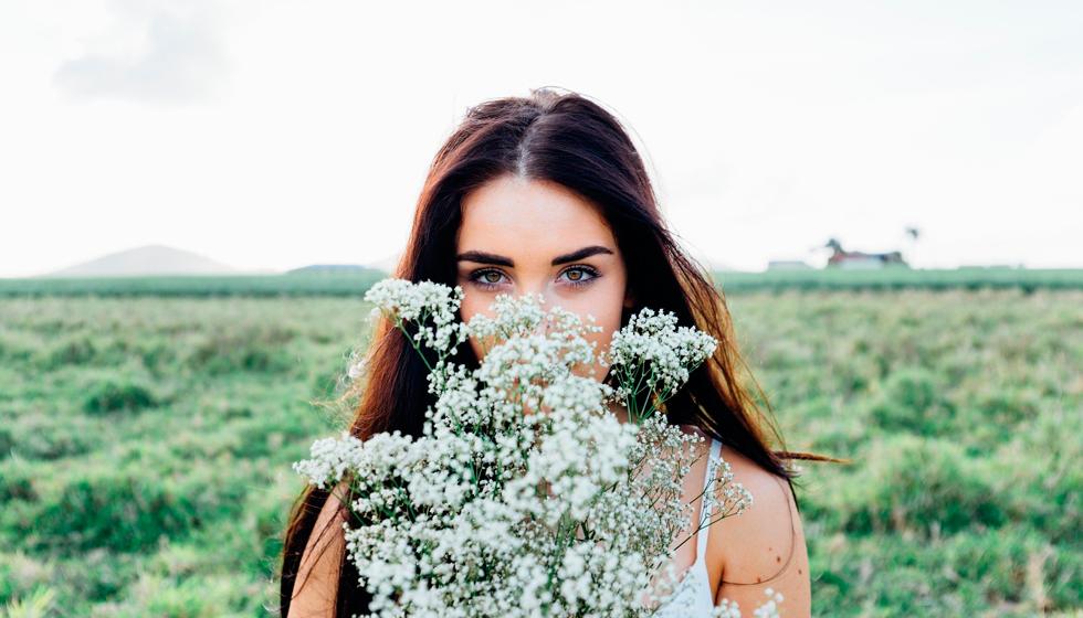 Женщина прячет лицо за цветами, глаза грустные
