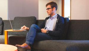 мужчина на диване с ноутбуком