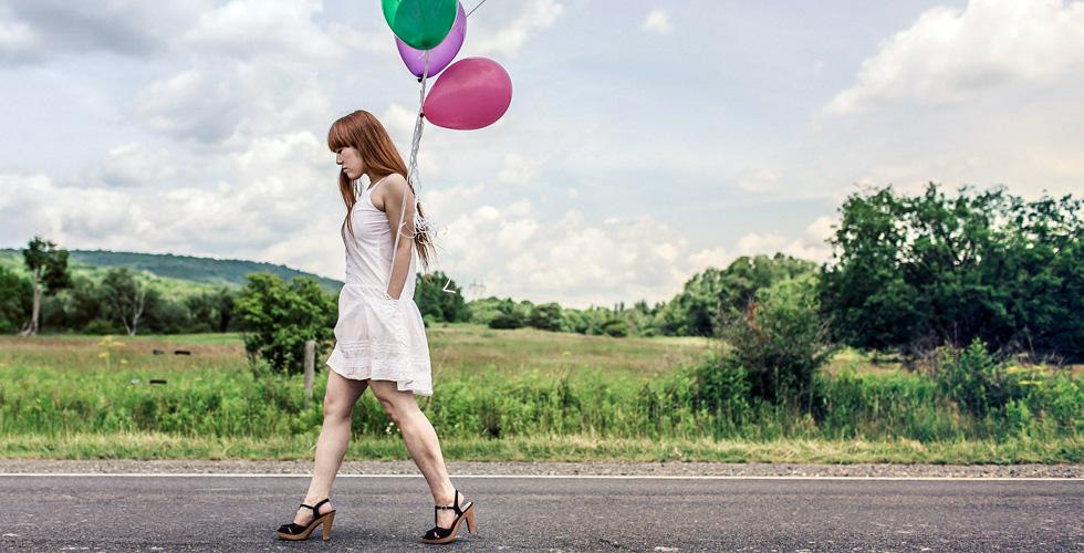 девушка с воздушными шариками грустно идет по шоссе