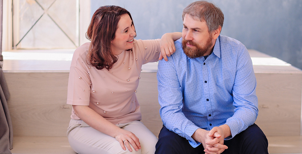 Яна Катаева с мужем сидят на диванчике