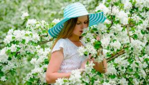 девушка нюхает цветущий кустарник