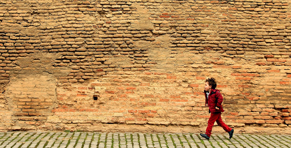 мальчик бежит вдоль кирпичной стены