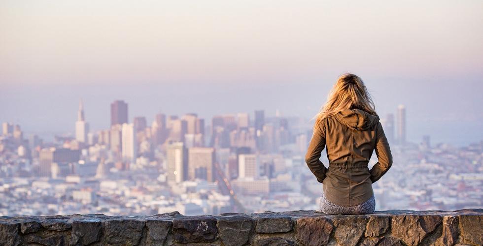Девушка одна сидит смотрит на город