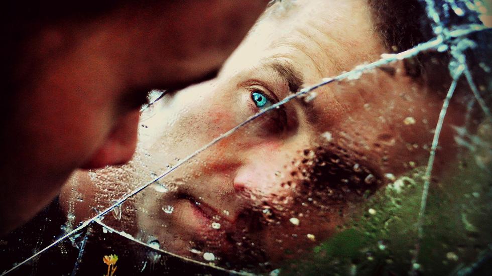 Лицо мужчины за разбитым стеклом