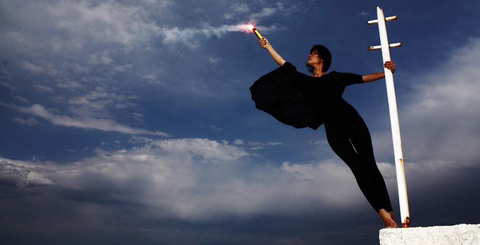 Девушка светит фонарем в хмурое небо