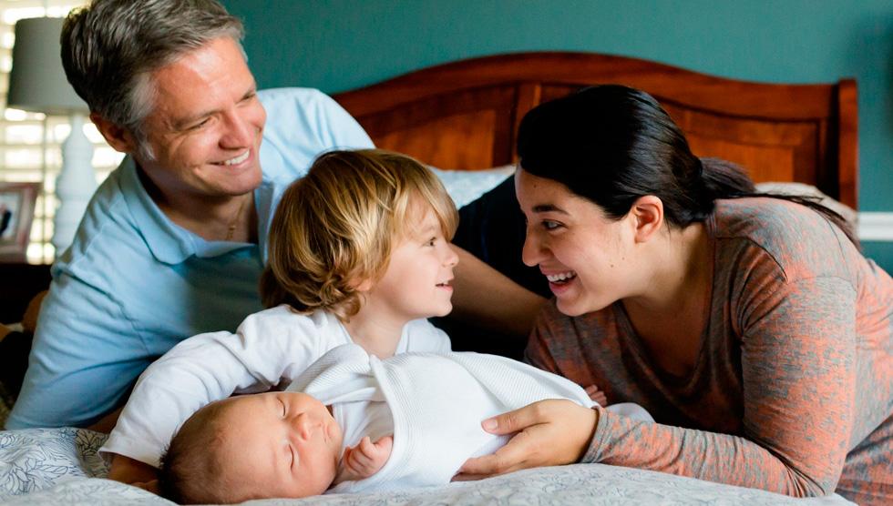 Муж и жена с детьми на кровати