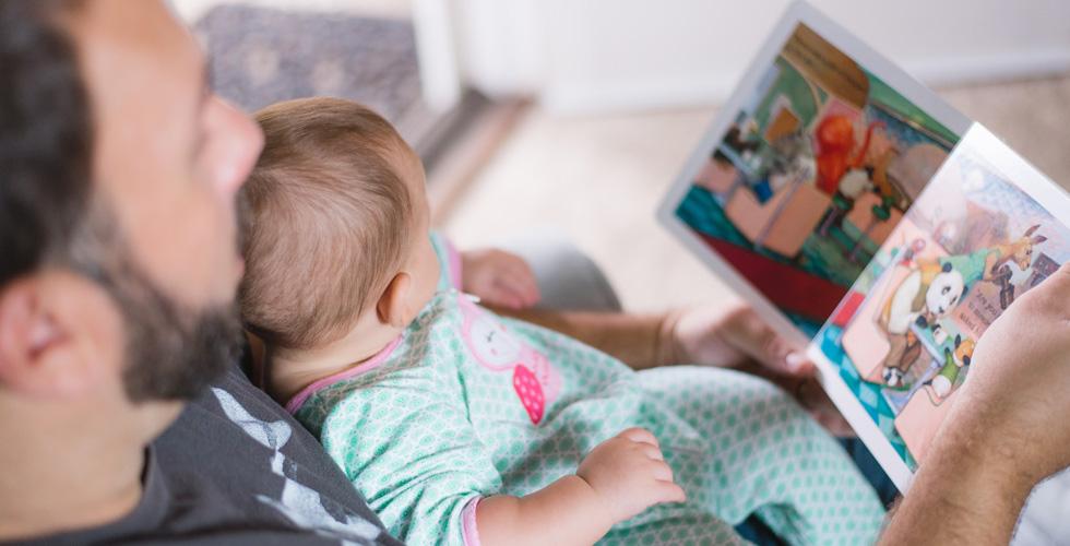 Мужчина с малышом смотрят книжку