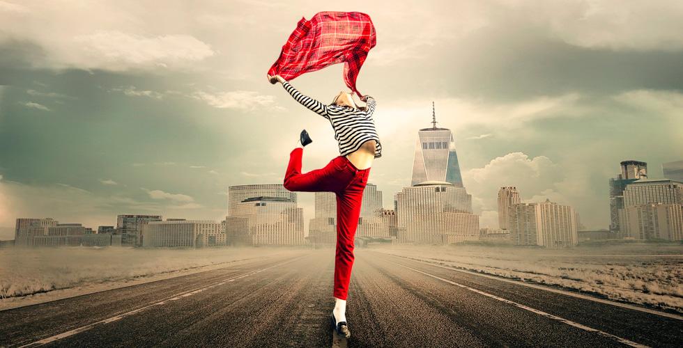 Девушка в танце на шоссе на фоне города
