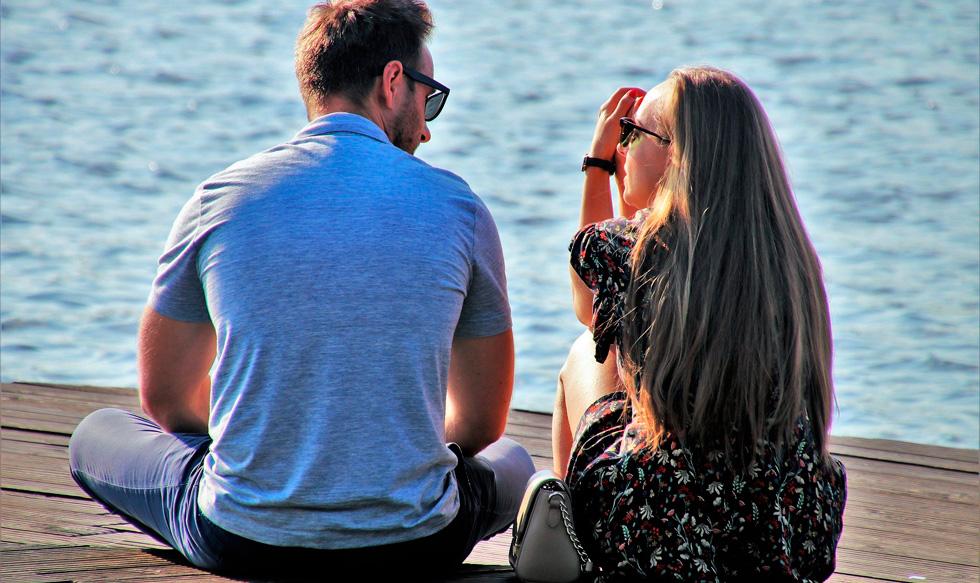Мужчина и женщина у воды разговаривают, вид со спины